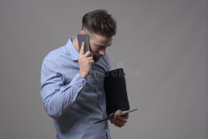 Bezige zakenmanbespreking op de telefoon en bekijken tablet terwijl het houden van laptop stock foto