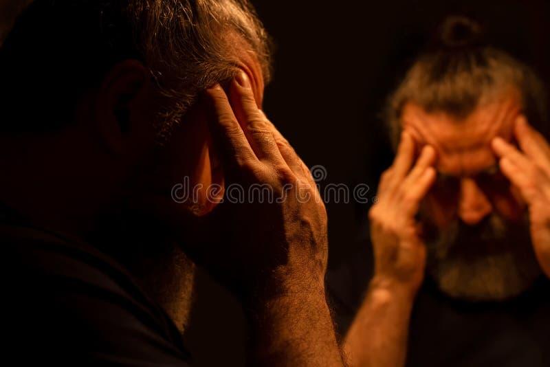 Bezinning die van de gebaarde mens in dark, zijn hoofd met zijn handen met pijnlijke uitdrukking houden royalty-vrije stock afbeelding