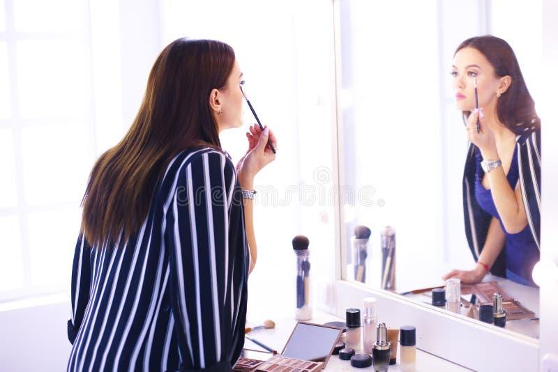 Bezinning die van jonge mooie vrouw die haar samenstelling toepassen, in een spiegel kijken stock afbeelding