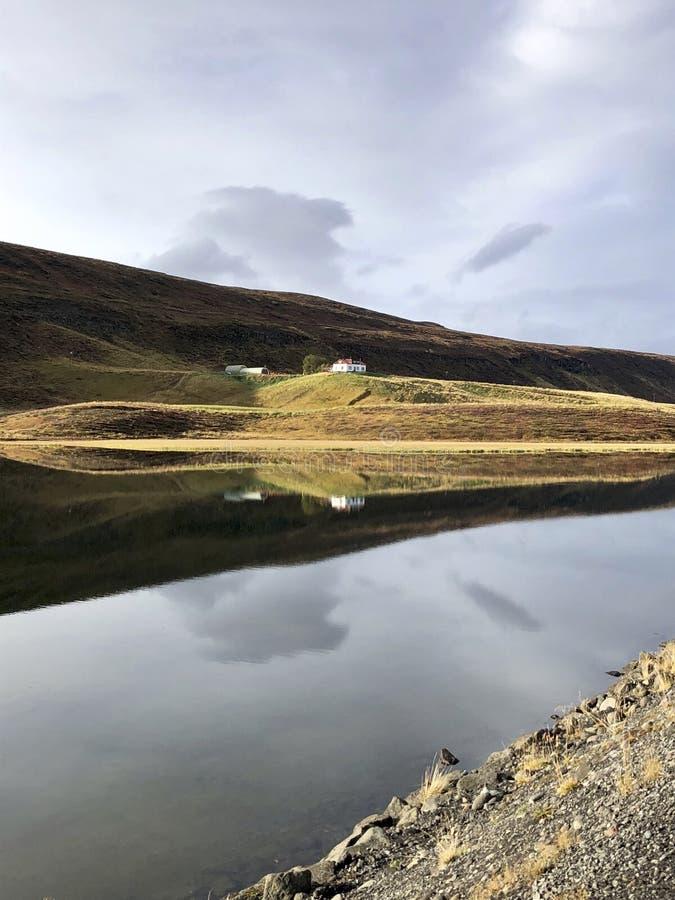 bezinning in het meer en de cabine van IJsland stock afbeelding