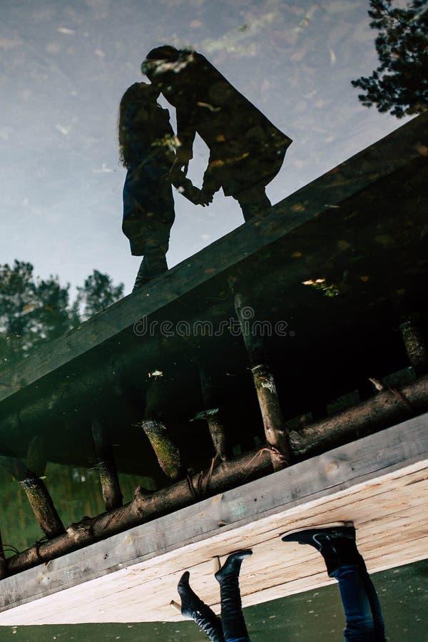 Bezinning in het water van een kerel en een meisje die zich op de rand van de pijler bevinden stock foto