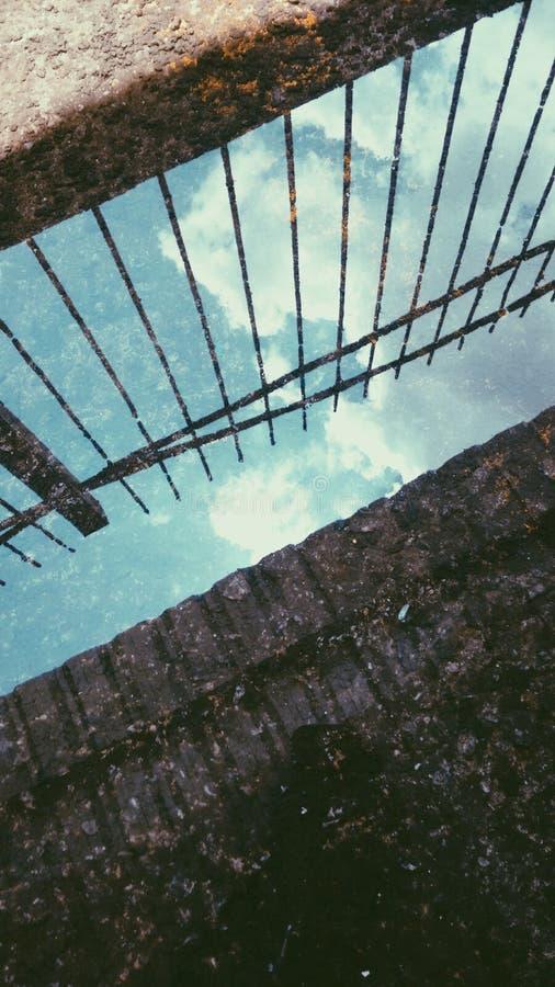 Bezinning van blauwe die hemel met wolken door water wordt gemaakt royalty-vrije stock afbeelding
