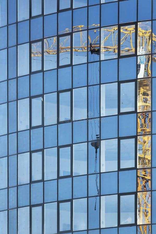 Bezinning van bouwkraan op het glas van de lange bureaubouw met meerdere verdiepingen stock afbeeldingen