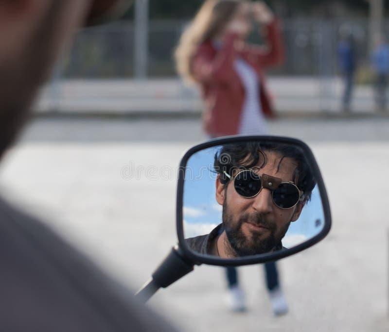 Bezinning van de mens met glazen en baard in een motorspiegel stock foto's