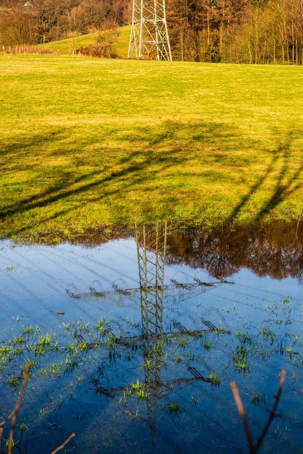Bezinning van een elektriciteits pylon en blauwe hemel in een vulklei op een weide stock foto's