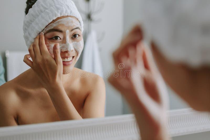 Bezinning van een vrouw die in badkamersspiegel gezichtspak toepassen royalty-vrije stock foto