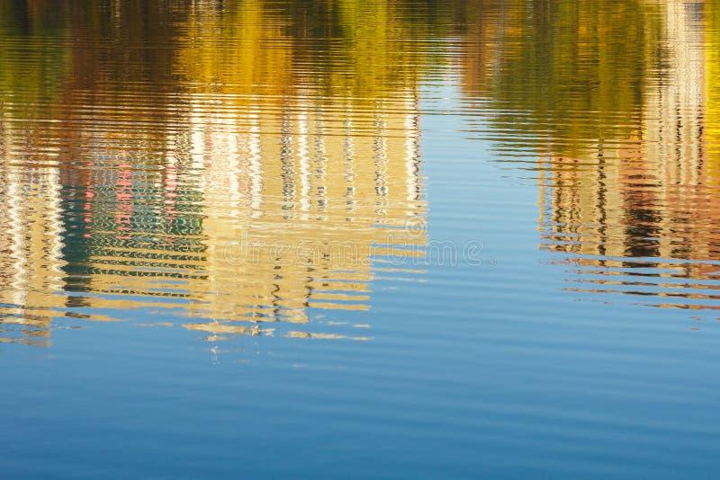 Bezinning van gebouwen en bomen in water, rivier, vijver, meer in de herfst, blauwe hemel stock fotografie