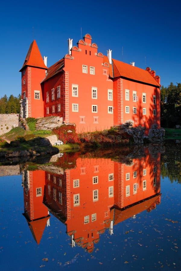 Bezinning van het rode kasteel op het meer, met donkerblauwe hemel, het kasteel Cervena Lhota, Tsjechische republiek van de staat stock afbeelding