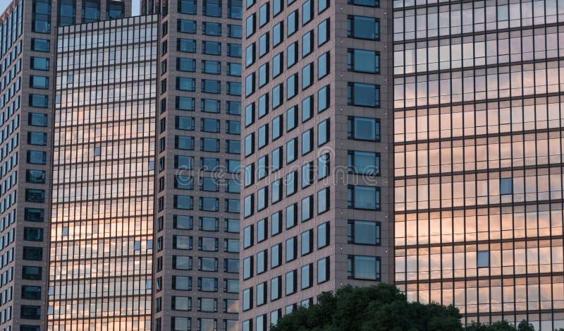 Bezinningen over vensters van zonsondergang warm licht in horizon en grote patronen in wolkenkrabbers, de moderne bureaubouw stock fotografie