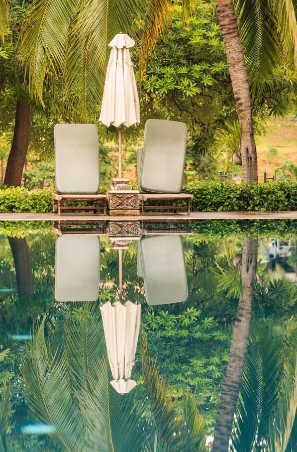Bezinningen van paraplu bij zwembad in tropisch stock afbeelding