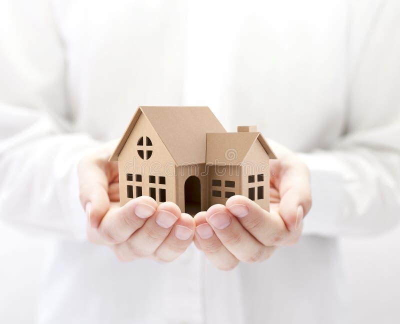 Bezit insurance De miniatuur van het kartonhuis in handen royalty-vrije stock afbeeldingen