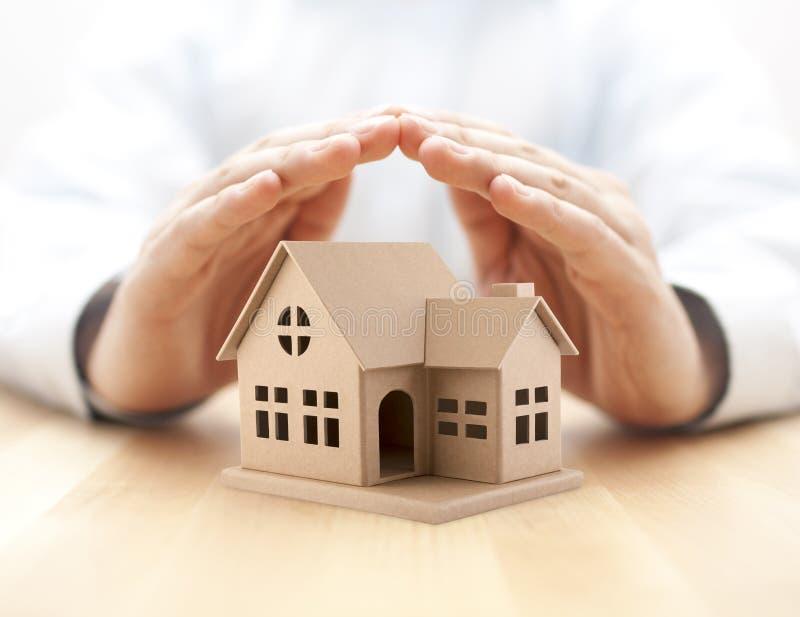 Bezit insurance Huisminiatuur door handen wordt behandeld die royalty-vrije stock foto