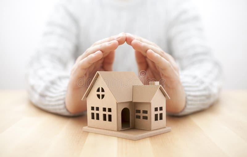 Bezit insurance Huisminiatuur door handen wordt behandeld die royalty-vrije stock foto's