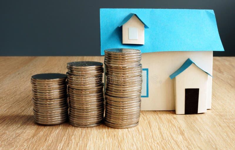 Bezitswaarde Model van huis en muntstukken stock foto