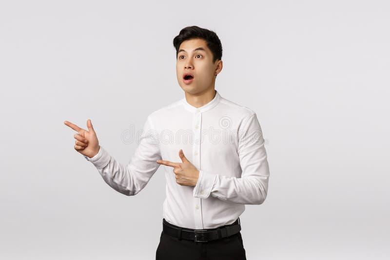 Bezmowy, zaskoczony i pod wrażeniem atrakcyjny azjatycki młody biznesmen w białej koszuli, czarne spodnie, otwarte usta obrazy royalty free