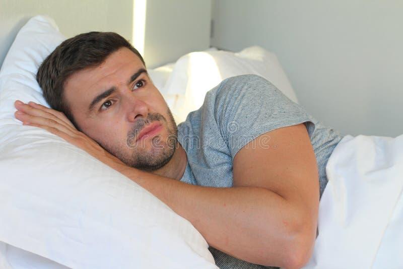 Beznadziejnego mężczyzna łgarski puszek w łóżku fotografia stock