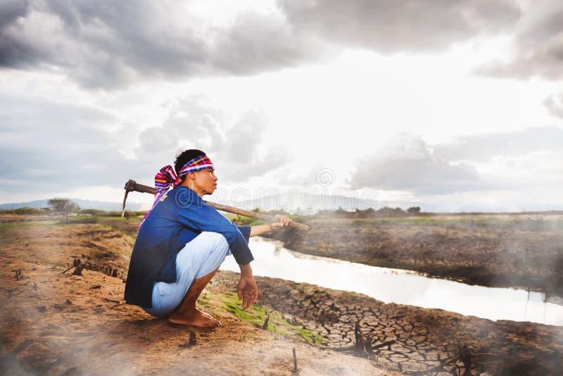 Beznadziejny Średniorolny obsiadanie na suchej ziemi z motyką na jego ramieniu i kontrparą od ziemi Globalne ocieplenie kryzys obraz royalty free