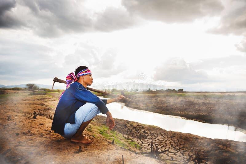 Beznadziejny Średniorolny obsiadanie na suchej ziemi z motyką na jego ramieniu i kontrparą od ziemi Globalne ocieplenie kryzys zdjęcia royalty free