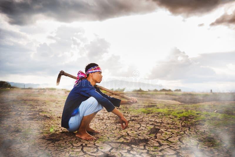 Beznadziejny Średniorolny obsiadanie na suchej ziemi z motyką na jego ramieniu i kontrparą od ziemi Globalne ocieplenie kryzys fotografia stock