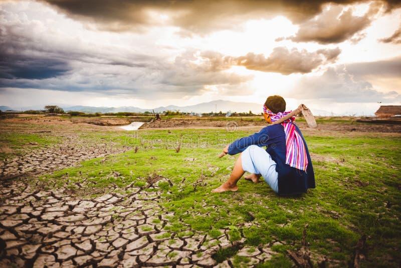 Beznadziejny Średniorolny obsiadanie na suchej ziemi z motyką obok on Globalne ocieplenie kryzys, obraz royalty free