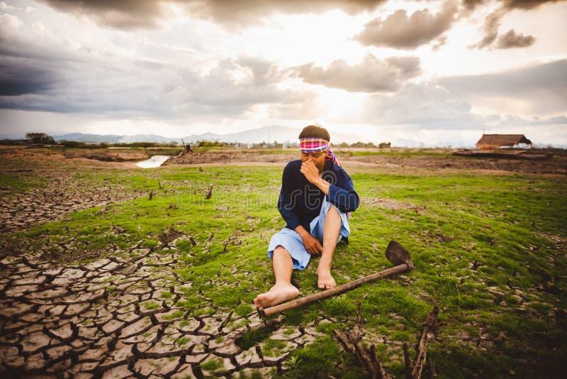 Beznadziejny Średniorolny obsiadanie na suchej ziemi z motyką obok on Globalne ocieplenie kryzys zdjęcie royalty free