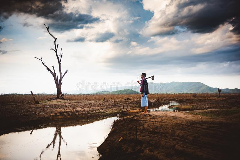 Beznadziejny i osamotniony rolnik siedzi na krakingowej ziemskiej pobliskiej osuszki wodzie obrazy stock