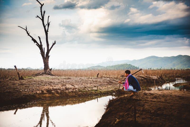 Beznadziejny i osamotniony rolnik siedzi na krakingowej ziemskiej pobliskiej osuszki wodzie obrazy royalty free