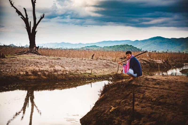 Beznadziejny i osamotniony rolnik siedzi na krakingowej ziemskiej pobliskiej osuszki wodzie zdjęcia stock