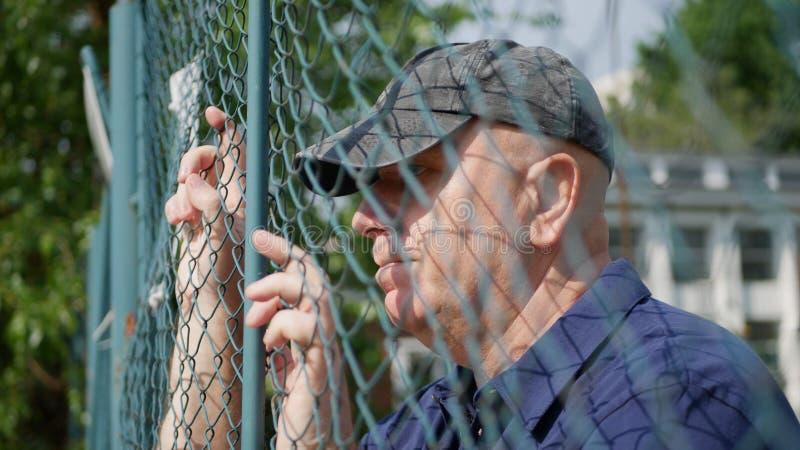 Beznadziejny mężczyzna Patrzeje Smutny Przez Kruszcowego ogrodzenia obraz royalty free