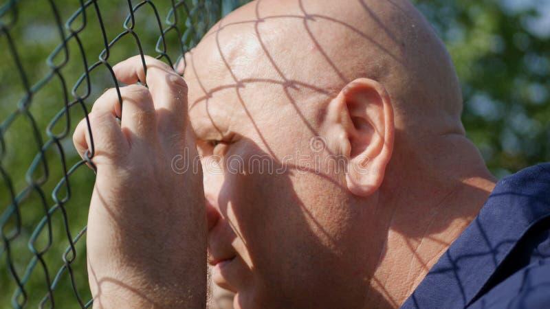 Beznadziejny mężczyzna Patrzeje Smutny Przez Kruszcowego ogrodzenia zdjęcia stock