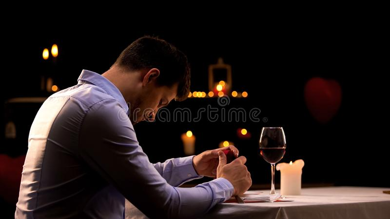Beznadziejny mężczyzny mienia pierścionek zaręczynowy, siedzi w restauracyjny samotnym, łama w górę zdjęcia stock