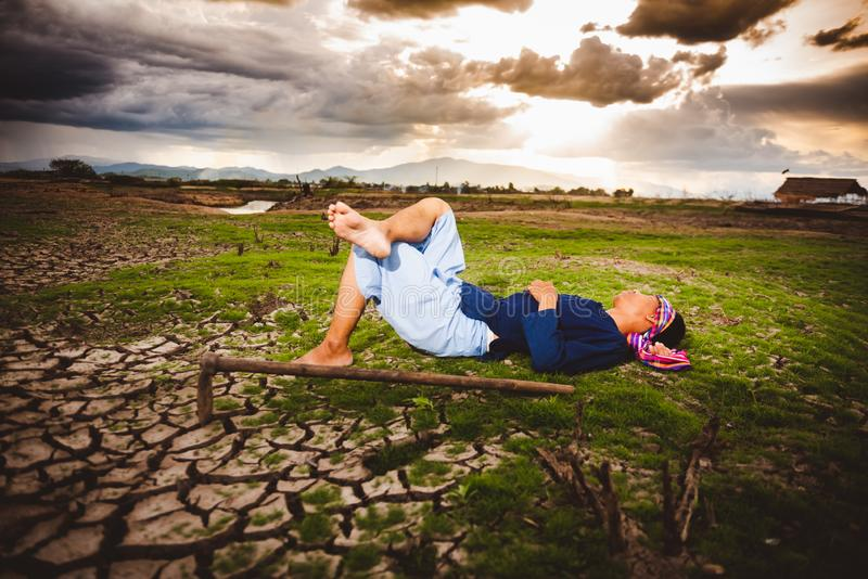 Beznadziejny rolnik kłaść w dół na suchej ziemi z motyką obok on Globalne ocieplenie kryzys obraz royalty free