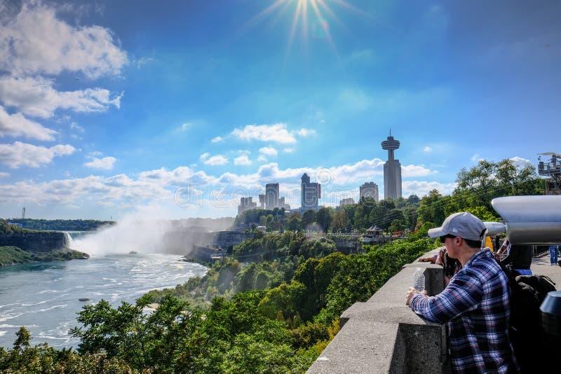 Bezoekers en toeristen gezien bekijkend de beroemde Niagara-Dalingen, Ontario stock foto's