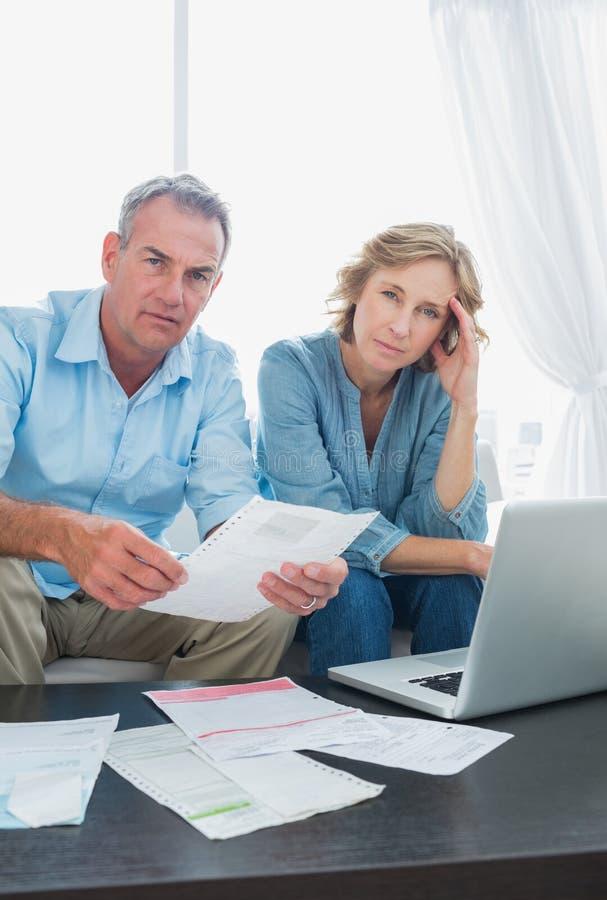 Bezorgd paar die hun rekeningen online met laptop betalen die bekijken stock fotografie