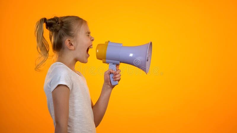 Bezorgd tienermeisje die in luidspreker, verlichtende spanning, kinderenrechten schreeuwen stock afbeelding