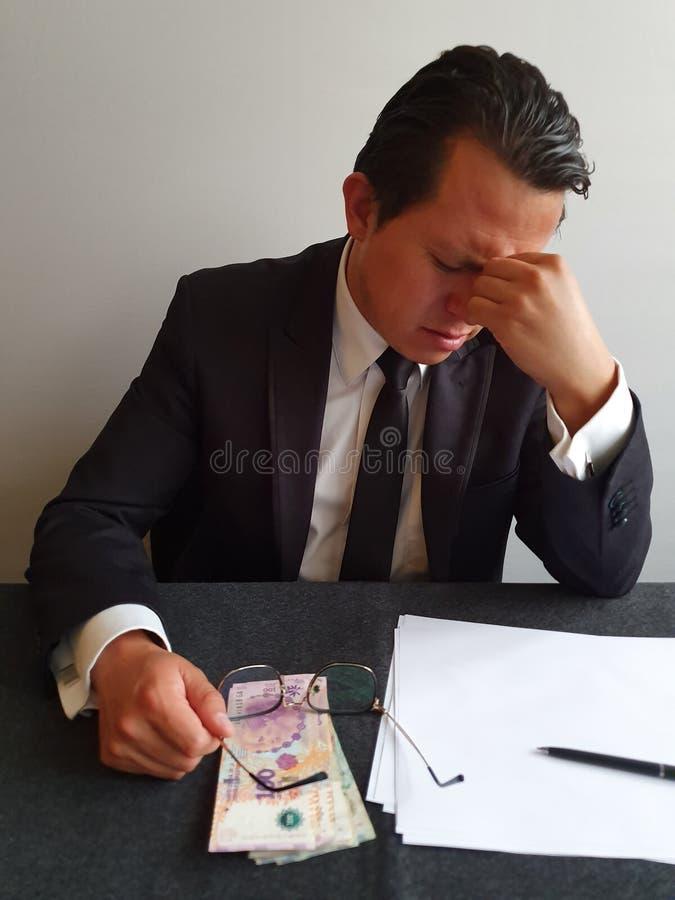 bezorgd zakenman met hand op zijn gezicht en Argentijns geld op tafel stock afbeelding