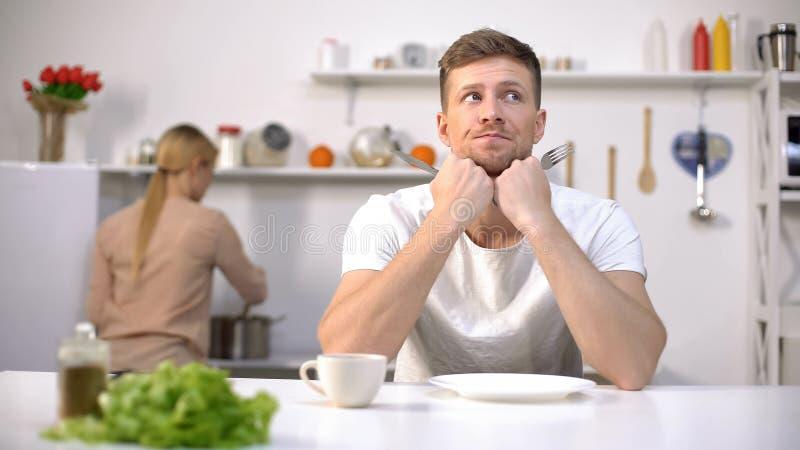 Bezorgde echtgenoot die op lunch, vrouw het koken op achtergrond, gebrek wachten aan tijd stock afbeeldingen