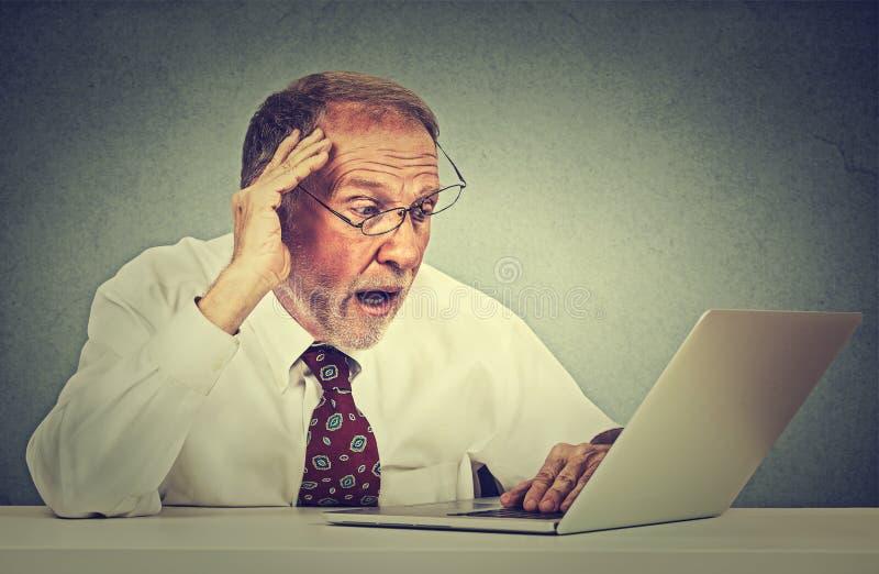 Bezorgde hogere mens die laptop het scherm bekijken die slecht nieuws met doende walgen emotie op zijn gezicht zien royalty-vrije stock fotografie
