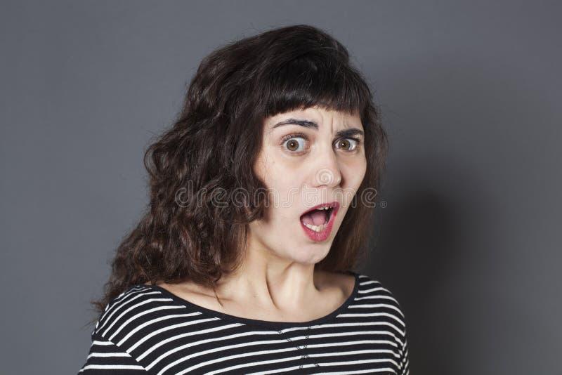 Bezorgde jonge donkerbruine vrouw die verrast kijken stock fotografie