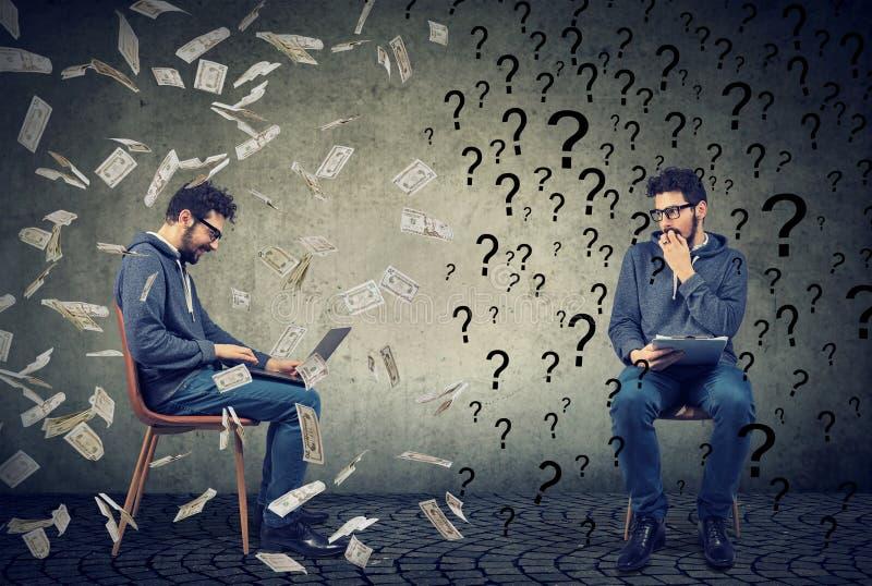 Bezorgde mens die met vragen succesvolle slimme kerel bekijken die aan laptop computer onder geldregen werken stock afbeelding