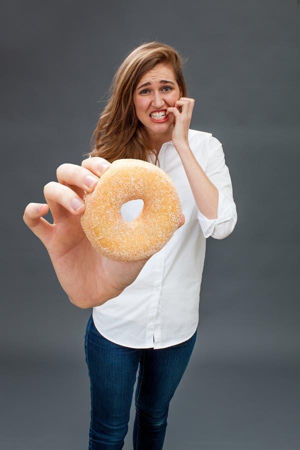 Bezorgde mooie jonge vrouw die haar vingers voor het snacking van gevaar bijten stock foto's