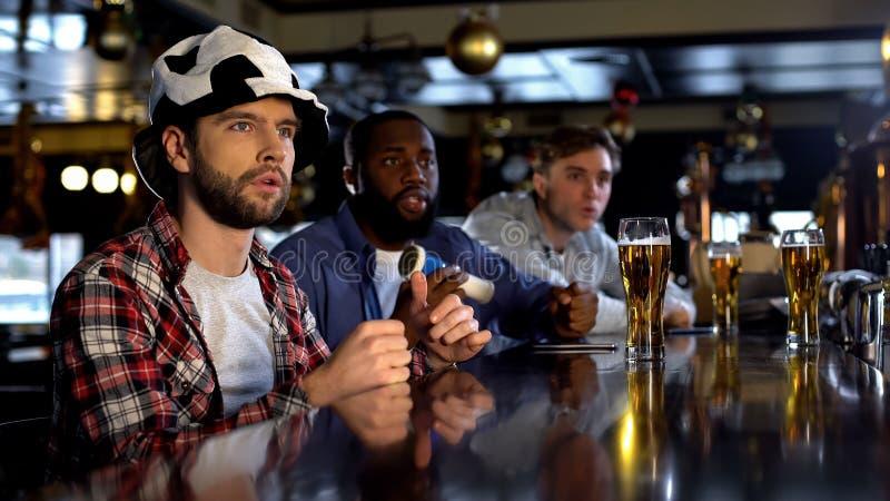 Bezorgde multiraciale mannelijke vrienden die op gelijke in bar letten, die voor teamdoel toejuichen stock foto's