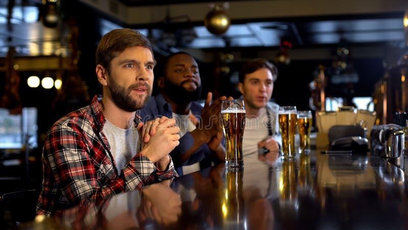 Bezorgde multiraciale vrienden die voor sporten spel in bar, het letten op spel op TV toejuichen stock foto's
