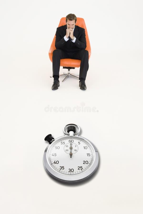 Bezorgde zakenmanzitting op stoel met chronometer voor hem die verlies van tijd vertegenwoordigen stock foto