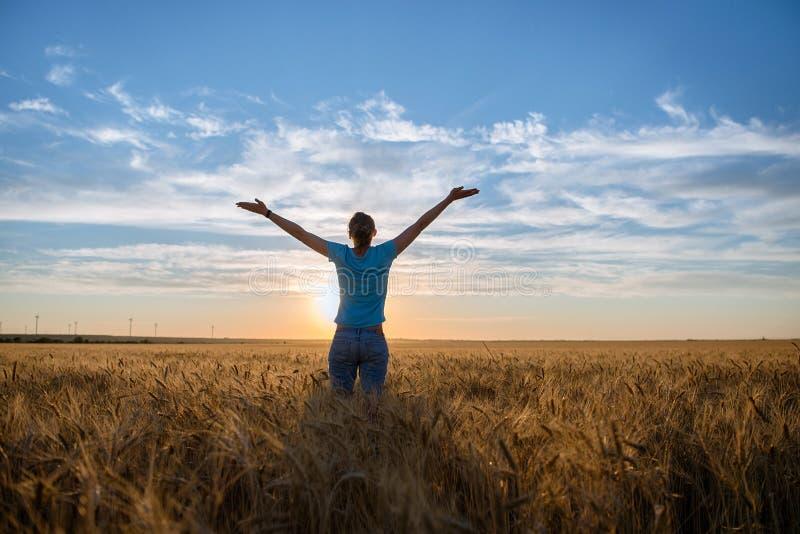 Bezpłatna Szczęśliwa kobieta Cieszy się naturę i wolność Plenerowych Kobieta z rękami szeroko rozpościerać w pszenicznym polu w z fotografia stock