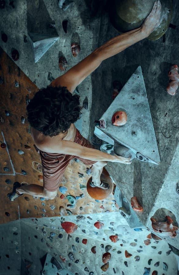Bezpłatny arywisty młody człowiek wspina się sztucznego głaz indoors zdjęcia stock