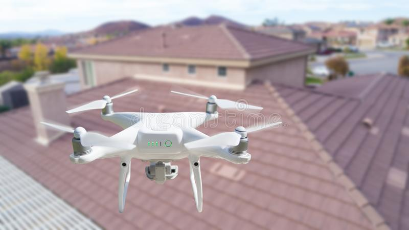 Bezpilotowy samolotu systemu UAV Quadcopter trute? W powietrzu Nad domem Sprawdza dach obrazy stock