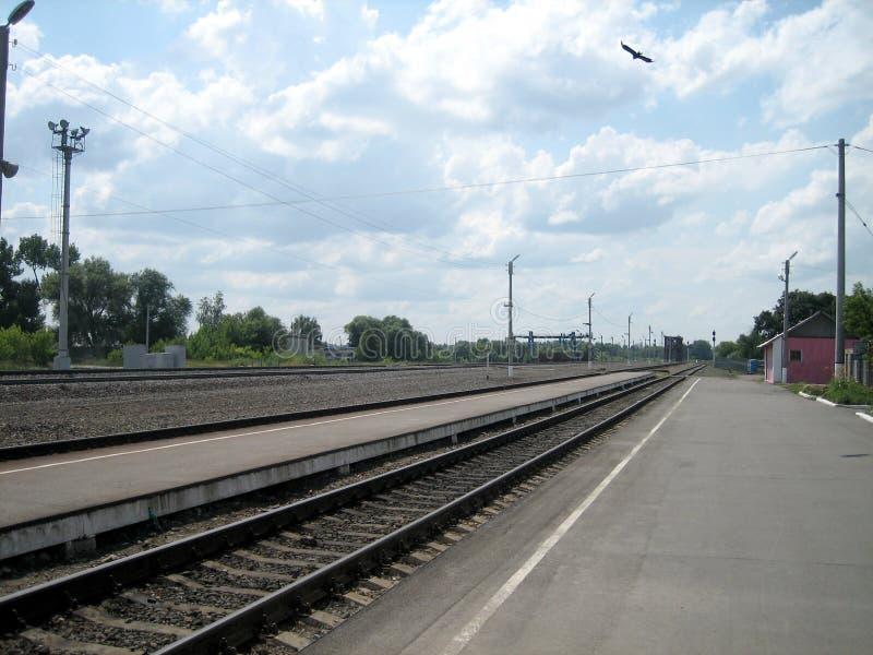 Bezpośredni tor kolejowy przez małą stację poza miastem w letni dzień Szyny stalowe układa się wzdłuż niskiego pomostu zdjęcie stock