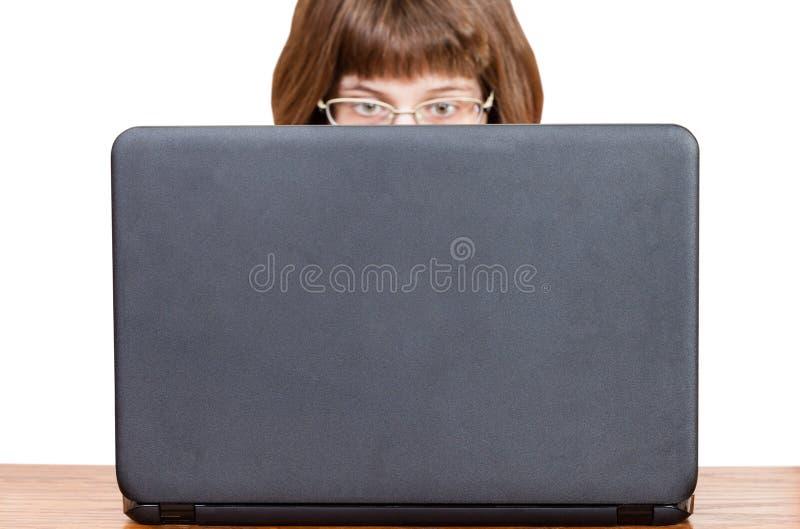 Bezpośredni widok dziewczyna z szkłami czyta od laptopu fotografia stock