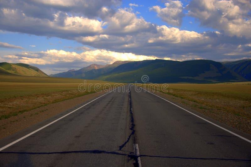 Bezpośrednia asfaltowa droga iść poza horyzont odpoczywa na pasmach górskich Kurai step, Altai, Rosja Krajobraz fotografia stock